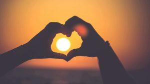 mains en coeurs avec un couché de soleil