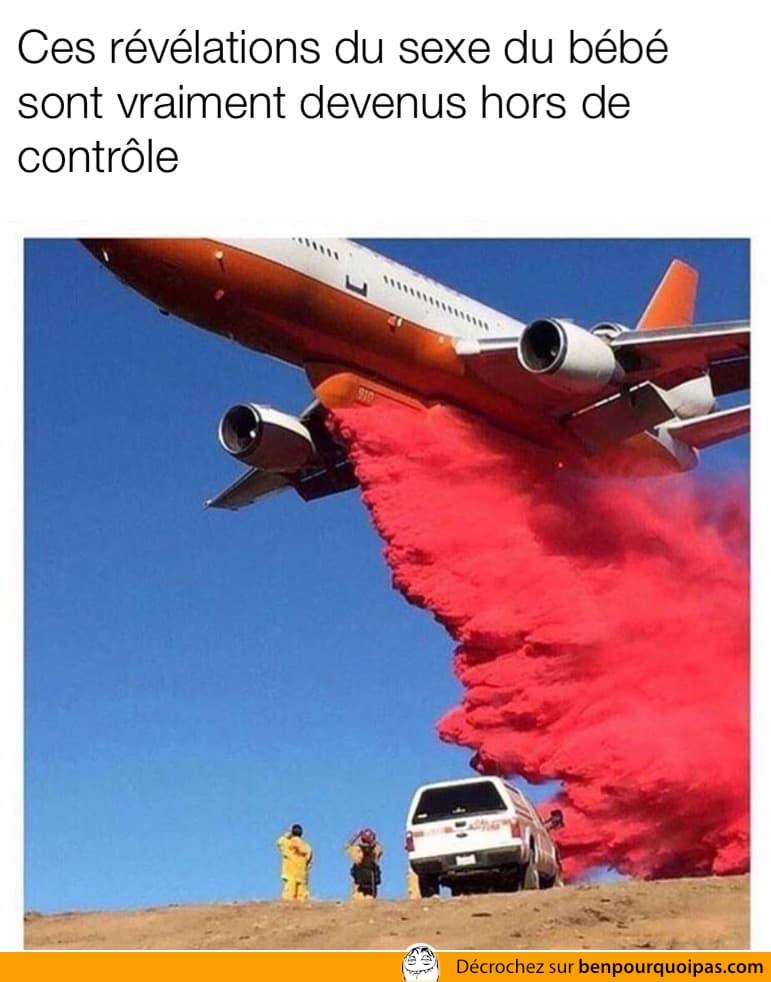 une avion laisse tomber un large nuage rouge