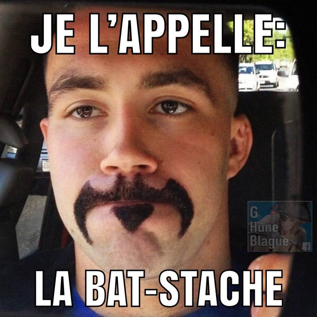Je l'appelle la Bat-Stache. Un homme a une moustage en forme du logo de Batman