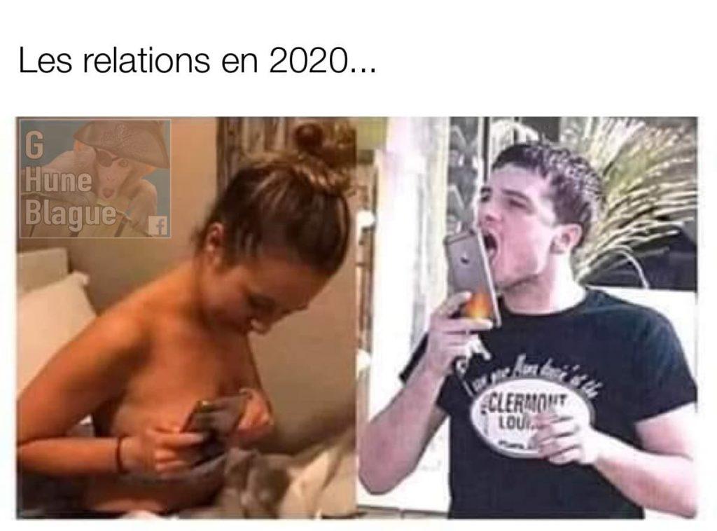 Les relations sexuelles en 2020 avec le confinement: un gars lèche une photo de seins dans son écran de téléphone